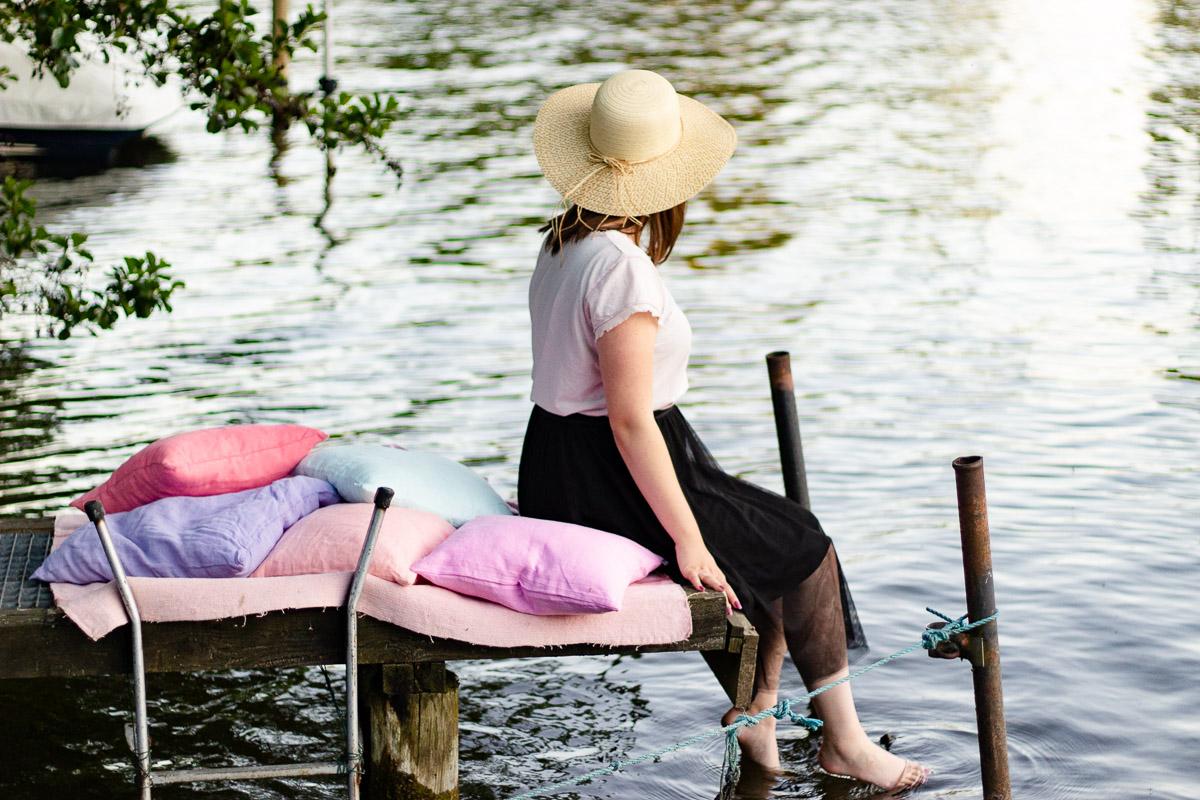 Sommerideen Frau auf Steg mit Leinenkissen