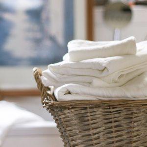 Leinenhandtücher in weiß im Korb auf Badewanne