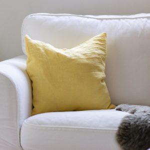 Kissenhülle aus Leinen in Gelbton Strohblume auf weißem Sofa
